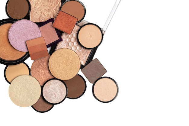 Pile of single eye shadows, bronzers, highlighters on a white background