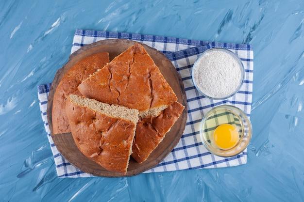 Un mucchio di pane a fette su una tavola accanto a uova e farina su un canovaccio, sulla superficie blu.