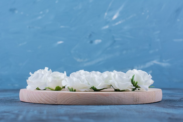 Pile of small white flowers placed on blue.