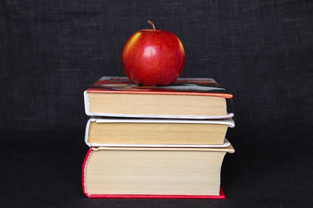 Pile stack of books with red apple on top, back to school concept