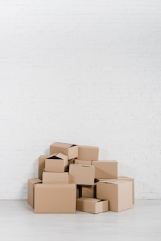 Pile of stacked cardboard boxes on floor against the white wall