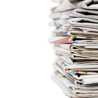 Pile of stacked generic folded newspapers on white background