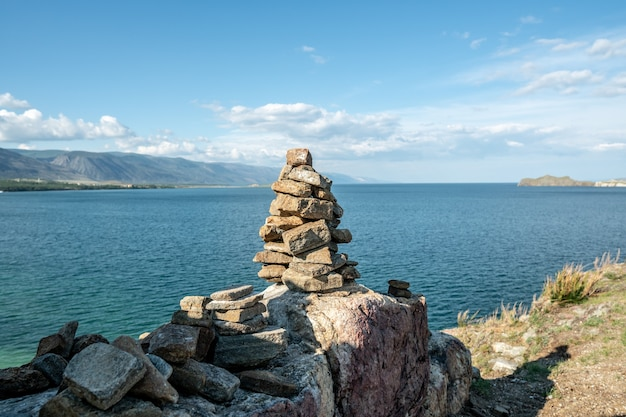 Pile of stones built in cairn on the background of lake baikal