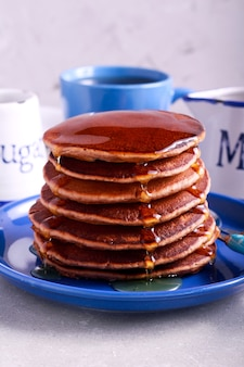 Pile of stout and chocolate pancakes with honey