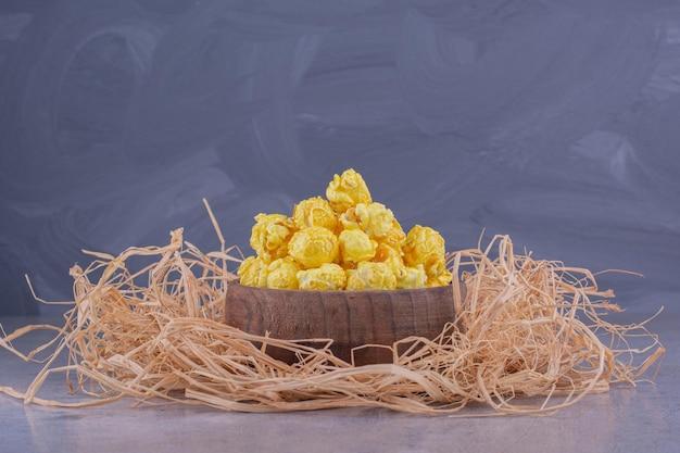 Un mucchio di paglia sotto una piccola ciotola di legno piena di caramelle popcorn su sfondo marmo. foto di alta qualità