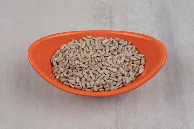 Mucchio di semi di girasole in una ciotola arancione.