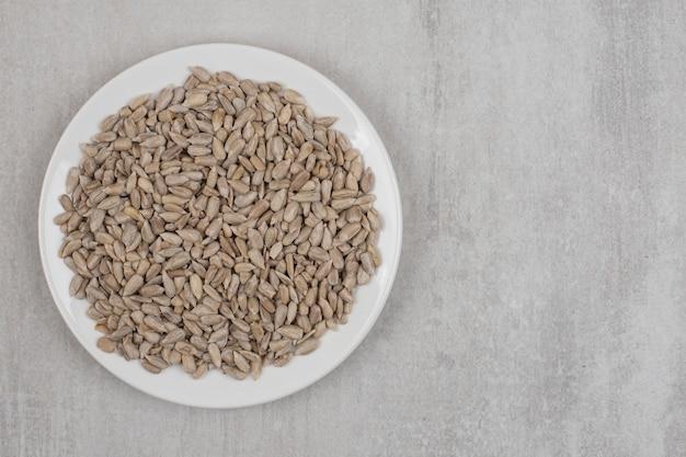 Mucchio di semi di girasole sul piatto bianco.