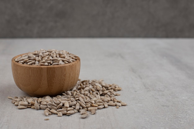 Mucchio di semi di girasole in ciotola di legno.