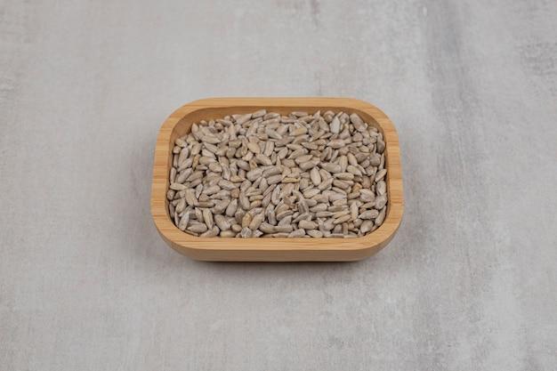 Mucchio di semi di girasole sul piatto di legno.