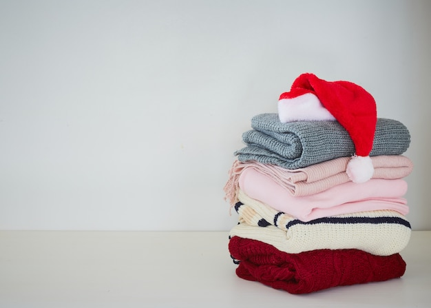 Pile sweater with santa hat on table