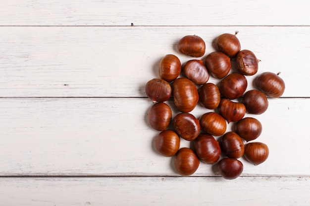 Pile of sweet chestnuts on white wooden background