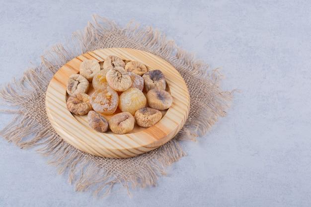 Pila di fichi secchi dolci immessi sul piatto di legno.