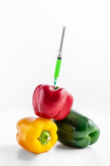 Pile of sweet peppers ans syringe with chemicals