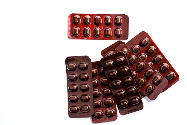 Pile of tablets pills medicine in light resistant blister pack on white background . vitamins and minerals tablets pills for pregnant women. ferrous fumarate anemia treatment tablets pills.