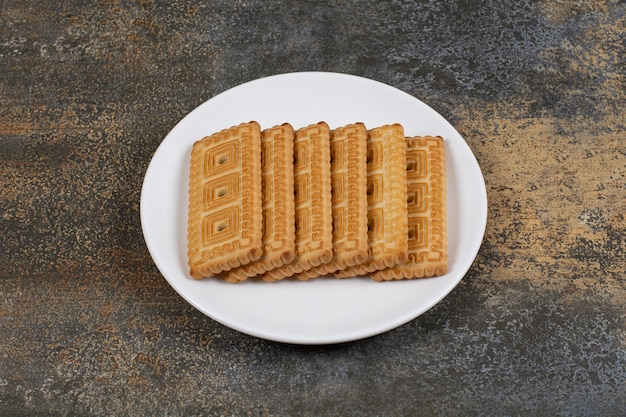 Pila di gustosi biscotti sulla piastra bianca.