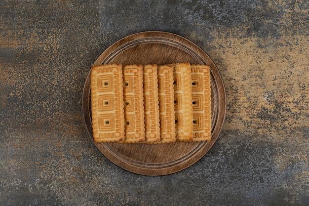 Pila di gustosi biscotti su tavola di legno.