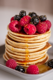 Pile of tasty ripe raspberries and blackberries and fresh honey on top of homemade pancake stack on grey plate cooked for breakfast