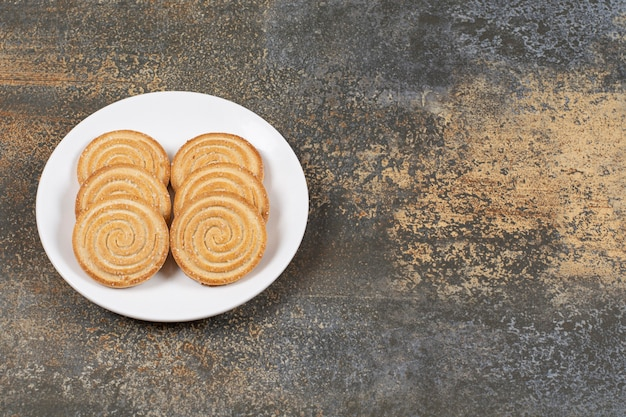 Pila di gustosi biscotti rotondi sulla piastra bianca.