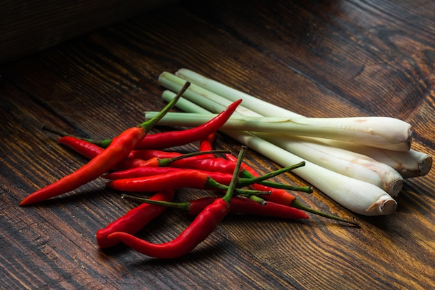 Pile of thai bird's eye chilis with lemongrass on a old wooden table