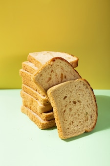 Pile of toast bread on one-ton background in green and yellow