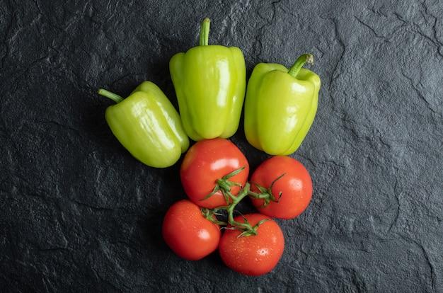 Pila di pomodori e pepe su sfondo nero