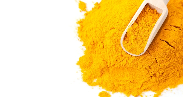 Pile of turmeric or curcuma powder with wooden scoop isolated wih copy space. top view
