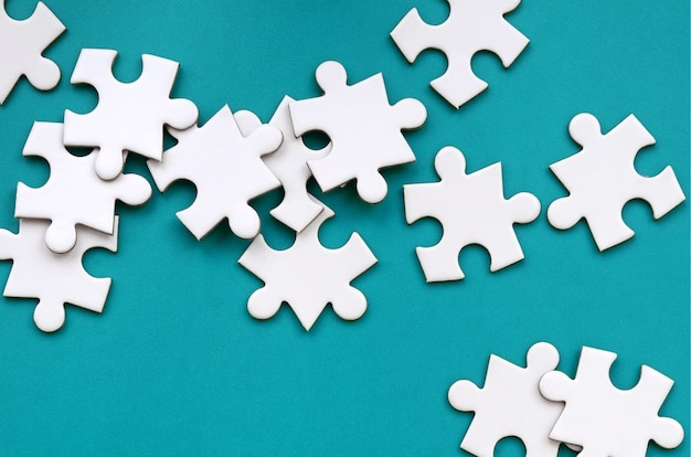 A pile of uncombed elements of a white jigsaw puzzle lies on the background of a green surface. texture photo with copy space for text