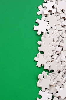 A pile of uncombed elements of a white jigsaw puzzle lies on a green surface