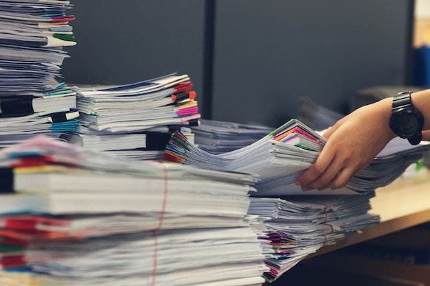 Pile of unfinished documents on office desk