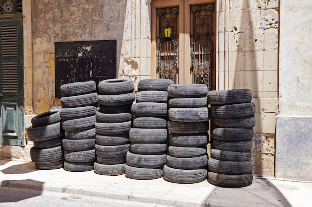 Pile of used car rubber tires near auto garage on street.