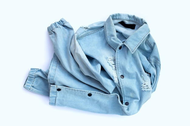 Pile of used jeans shirt on white surface