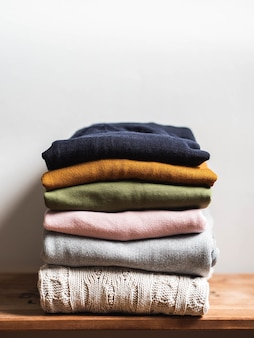 Pile of varicolored autumn clothes on a wooden background, sweaters, knitwear, copy space