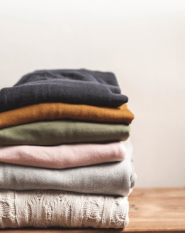 Pile of varicolored autumn clothes on wooden background, sweaters, knitwear