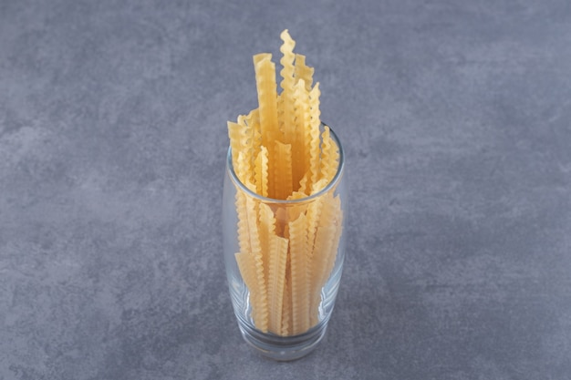 Pile of various-shaped dry pasta in glass.