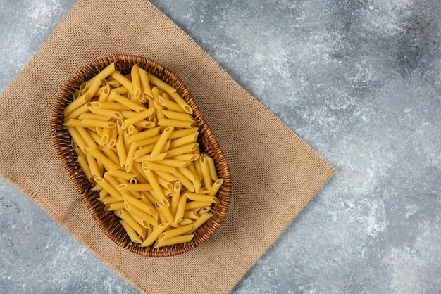 Pila di vari pasta secca cruda nel cesto di vimini e ciotole di legno.