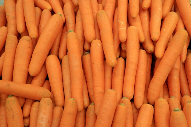 Pile of vibrant orange color carrots for background