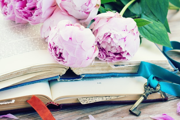 Pile of vintage old books with pink  flowers and key stacked on table
