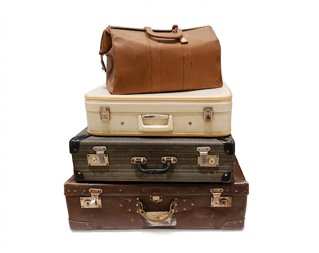 Pile of vintage suitcases isolated. old travel luggage
