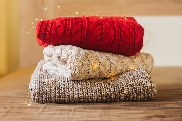 A pile of warm sweaters on the wood bed decorated with lights.