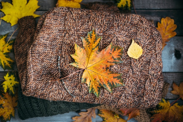A pile of warm sweaters on a wooden table with autumn leaves, knitwear, space for text, autumn winter concept.