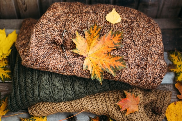 A pile of warm sweaters on a wooden table with autumn leaves