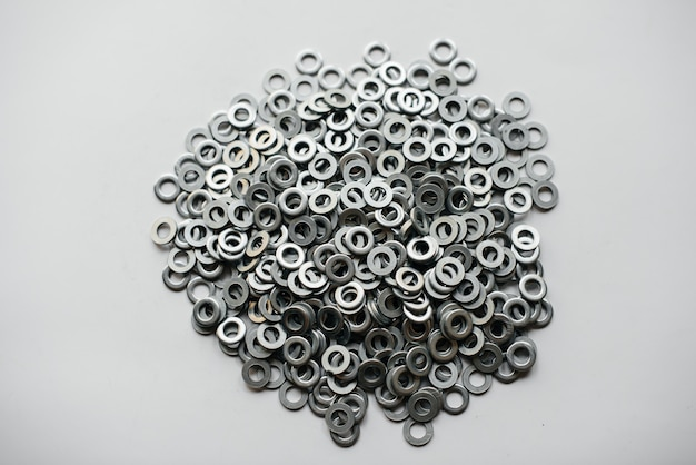 Pile of washers, bolts and nuts on a light background close-up.