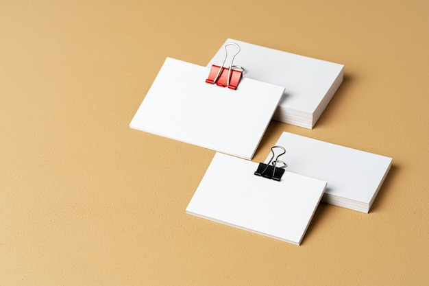 Pile of white businesscards with a clip on beige background
