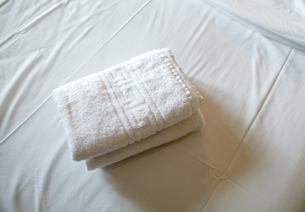 Pile of white clean towels on the bed