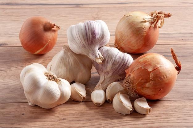 Pila di cipolle intere e bulbi di aglio e chiodi di garofano su un tavolo di legno