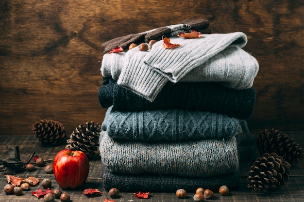 Pile of winter sweaters with an apple