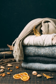 Pile of winter sweaters with leaves