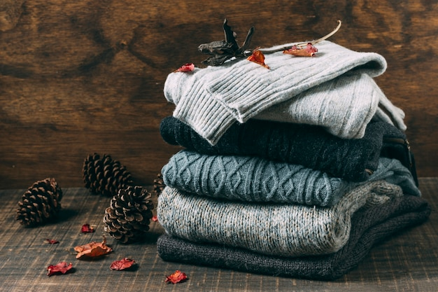 Pile of winter sweaters with pine cones
