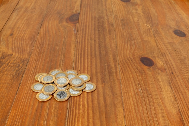 A pile with a lot of real brazilian money coins on a wood table