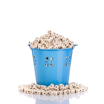Pile of wooden alphabet in small blue metal bucket.